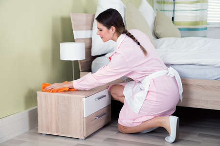 hotel room: Young Female Housekeeper Cleaning Nightstand In Hotel Room Stock Photo