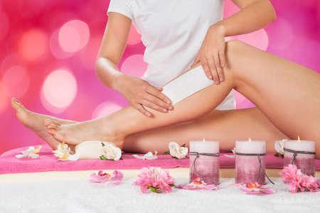depilacion con cera: Sección media de esteticista depilación pierna de la mujer con la tira de cera en el salón