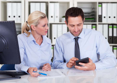 Male and female accountants calculating finance together at desk in office Stok Fotoğraf
