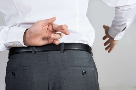 crossing fingers: Rear view of businessman crossing fingers behind back while offering handshake against white background Stock Photo