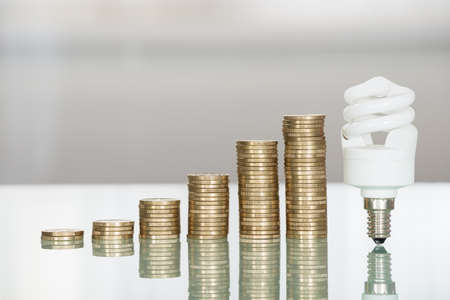 bills: Close-up Of Fluorescent Light Bulb And Stacked Coins On Desk