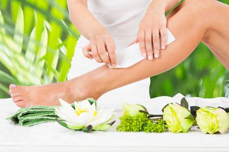 piernas: Sección media de esteticista depilación pierna de la mujer con la tira de cera en el spa de belleza