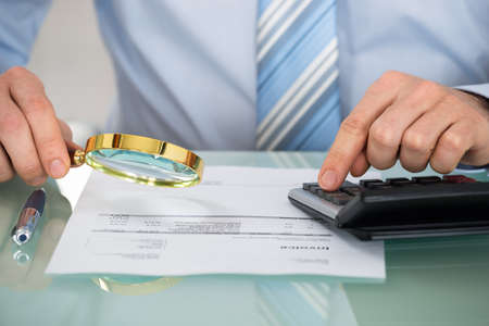 fraud: Close-up Of Businessman Checking Invoice With Magnifying Glass At Desk