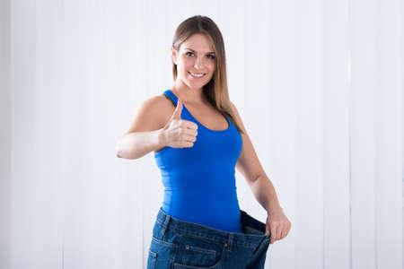 mujer gorda: Feliz mujer joven que muestra su Pérdida de peso con el uso de pantalones vaqueros viejos