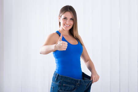 Happy Young Woman Showing Her Weightloss By Wearing Old Jeans