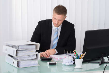 account executive: Young Businessman Calculating Tax At Office Desk Stock Photo