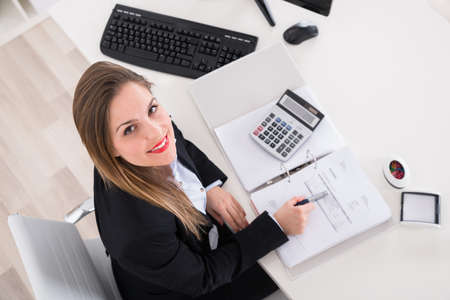 executive woman: Young Happy Businesswoman Calculating Tax At Office