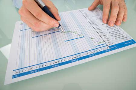 Primer plano de un hombre de negocios con la carta de Gantt El trabajo de la pluma