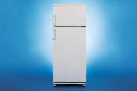 refrigerator: Photo of closed refrigerator isolated over blue background Stock Photo