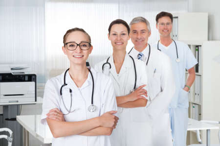 Portrait of confident medical staff standing with doctor in hospital photo