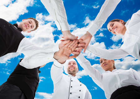 Low angle view of waiters and waitresses stacking hands against sky