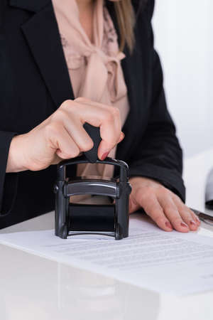 stamper: Close-up Of Businessperson Hand Using Stamper On Document Stock Photo
