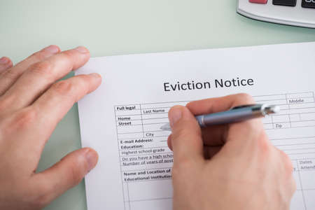 evicted: Close-up Of Person Hand Filling Eviction Notice Form