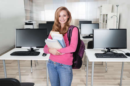 Portrait of happy young female college student with books in computer class photo