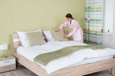 housekeeper: Young Female Housekeeper Arranging Pillow On Bed In Room