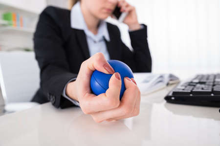 Jonge Onderneemster Die Stressball Pressed While Talking On Mobile Phone At Desk
