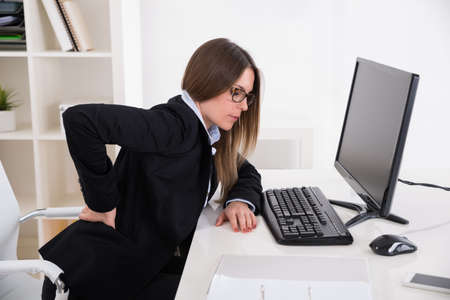 back ache: Young Businesswoman With Backpain Sitting On Chair At Workplace
