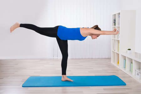 stretch: Young Female Doing Yoga On Exercise Mat In Her Living Room