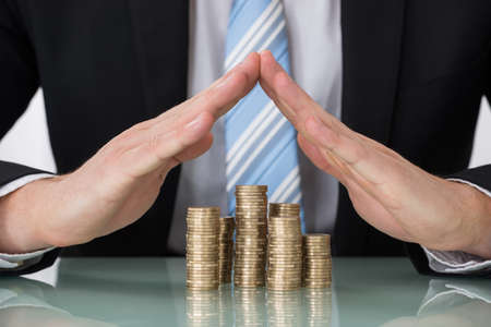 financial protection: Close-up Of Businessperson Saving Pile Of Coins Stock Photo