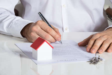 signing authority: Midsection of businessman signing house contract at office desk