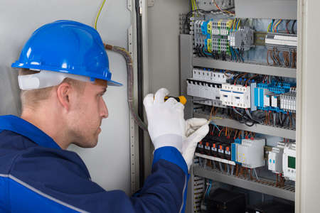 Male Electrician Working On Fusebox With Screwdriver Stock Photo