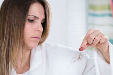 loose hair: Portrait Of A Young Woman Suffering From Hairloss Stock Photo