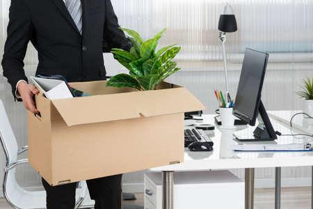 Buik van zakenman die kartonnen doos bij de balie in het kantoor