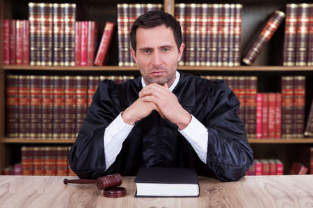 Portrait of serious judge thinking while sitting at desk in courtroom Foto de archivo