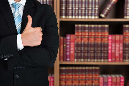 account executive: Midsection of lawyer gesturing thumbs up against books in shelves