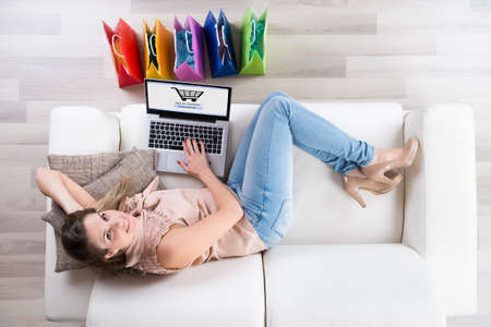 work from home: Young Happy Woman On Sofa Shopping Online With Laptop Stock Photo