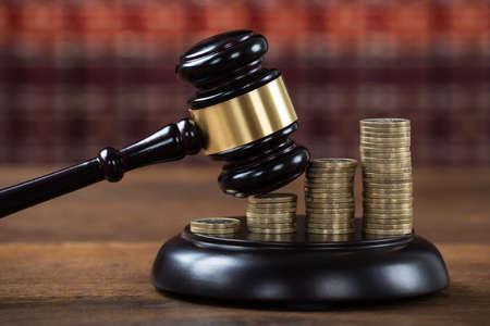 gerechtigkeit: Nahaufnahme von Holzhammer auf gestapelten Münzen am Tisch im Gerichtssaal getroffen zu