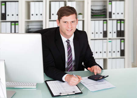 account executive: Portrait of confident male accountant using calculator at desk in office