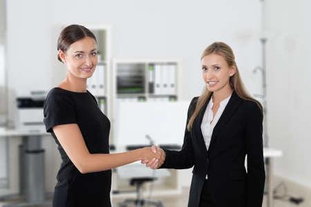 Portrait de femmes d'affaires se serrant la main en se tenant debout dans le bureau