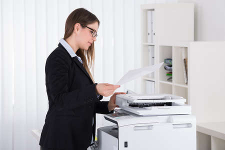Young Beautiful Businesswoman Using Copy Machine In Office