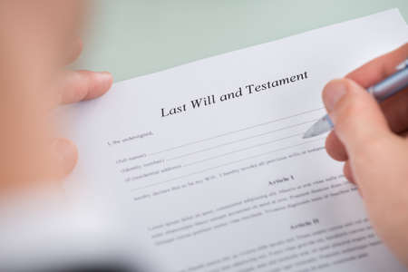 testament: Close-up Of Person Hand Over Last Will And Testament Form