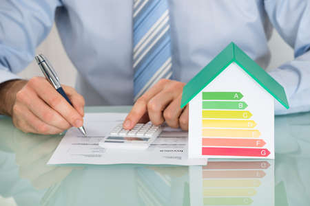 Close-up d'homme d'affaires Calcul de l'efficacité énergétique Taux Of House Dans Office Banque d'images