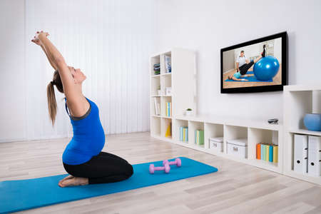 pregnancy yoga: Young Pregnant Woman Exercising In Front Of Television At Home