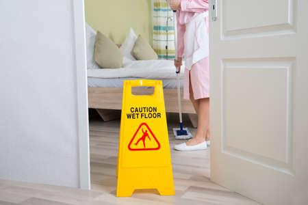 advertencia: Limpieza diaria de sexo femenino en una limpieza uniforme suelo en la habitación Foto de archivo