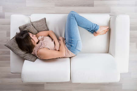 hormones: High Angle View Of Young Woman Napping On Sofa Stock Photo