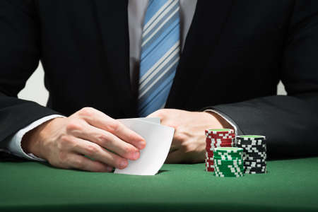 poker player: Close-up Of Poker Player Hand With Cards And Chips Stock Photo