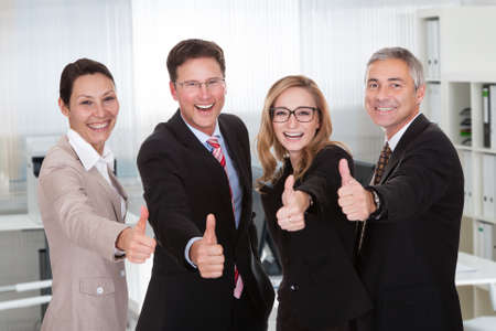 Portrait of multiethnic business people gesturing thumbs up while standing in office photo