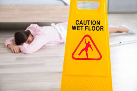 fainted: Close-up Of A Wet Floor Sign With Fainted Housekeeper Lying On Floor