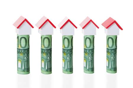 billets euro: Les maquettes de maisons dispos�es sur des billets en euros lamin�s sur le fond blanc