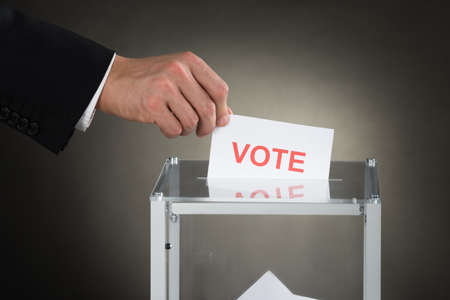 voting box: Close-up Of A Businessperson Hand Putting Vote Into Ballot Box Stock Photo