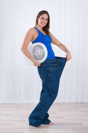 cuerpo femenino: Mujer joven delgada con un peso de la máquina El uso de pantalones vaqueros grandes Foto de archivo