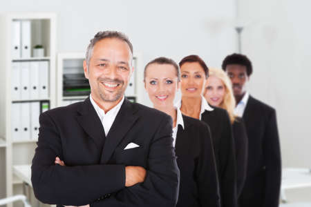 Multiethnic confident business people standing in row at office photo