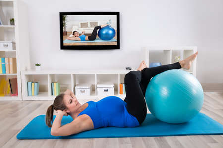pregnancy yoga: Young Pregnant Female Exercising In Front Of Television Stock Photo