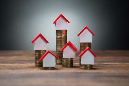 house prices: House models on stacked coins at wooden table