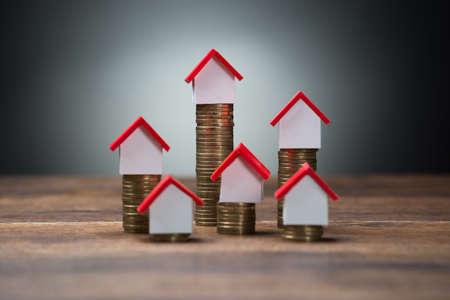 Huis modellen op gestapelde munten op houten tafel