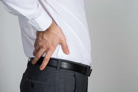 ache: Rear view of businessman suffering from back ache against white background